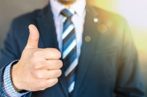 A man in a suit makes a thumbs up.